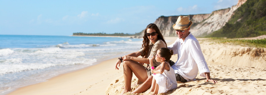 family sitting on gorgeous beach with cliffs